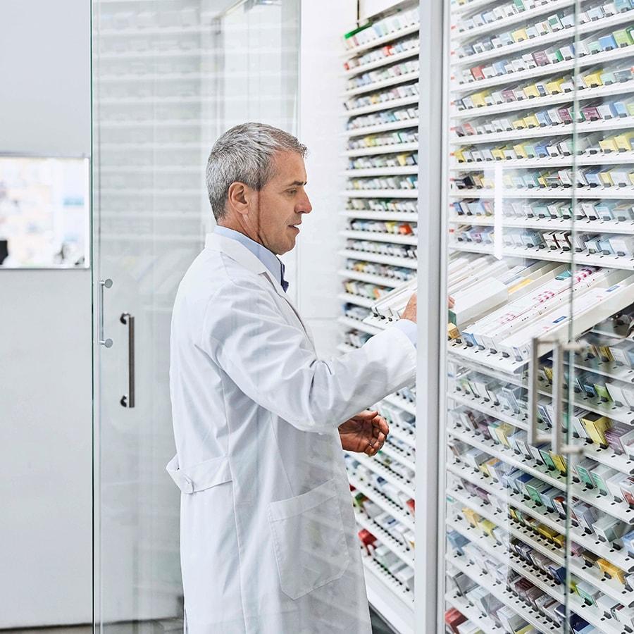 Pharmacist getting drugs off of a shelf