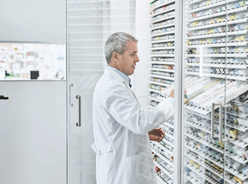 Pharmacist looking at medicines in a cabinet