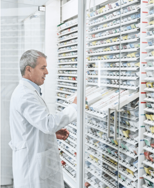 Pharmacist standing in-front of shelves full of different medicines